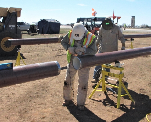 Reliable team members fitting two pieces of a fuel pipeline together.